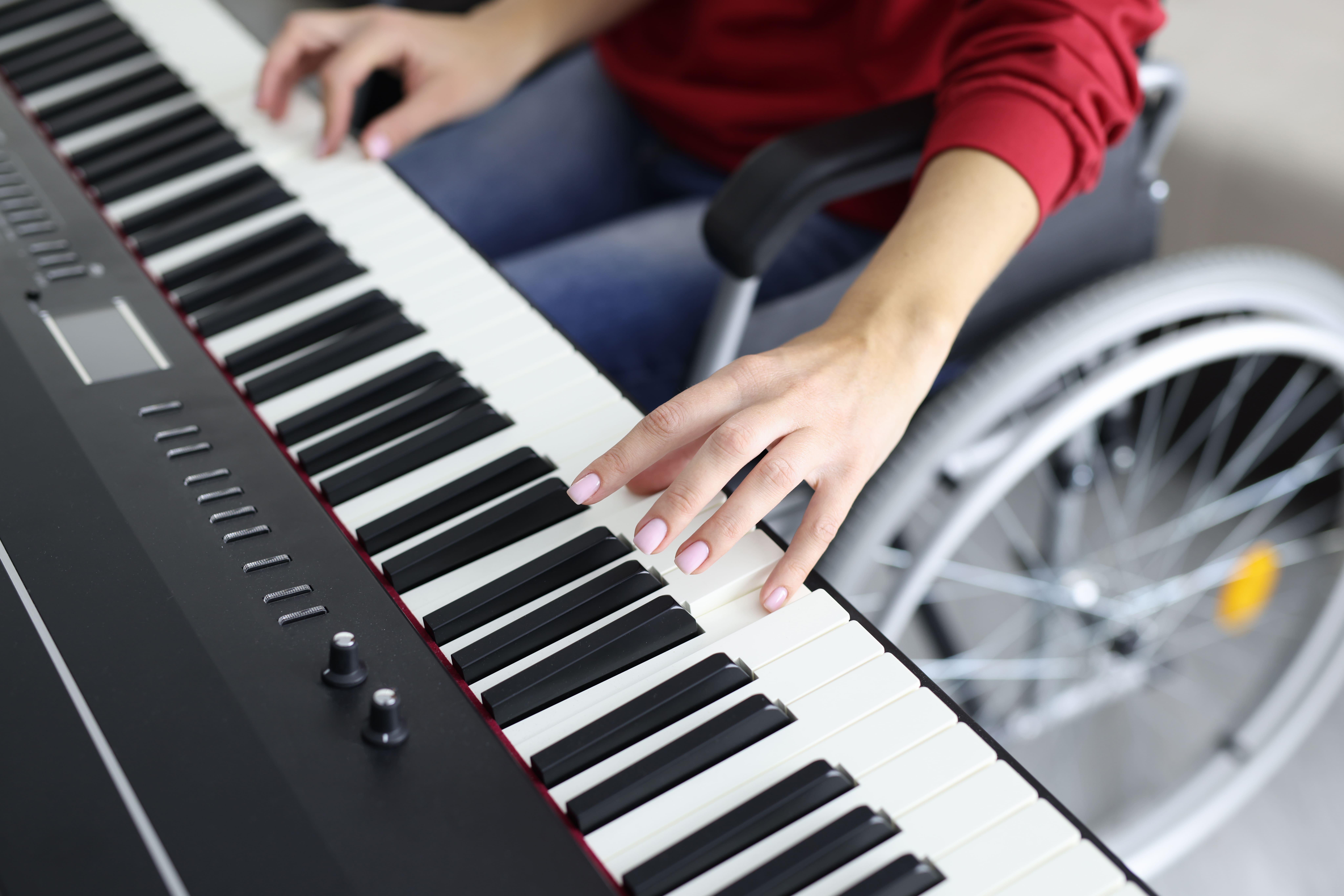 Une femme handicapée dans une chaise roulante joue du piano dans les espaces partagés de la résidence de Saint-Laurent-du-Var.